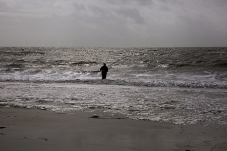 hombre pescando: Man fishing by the seashore, Vendee, France