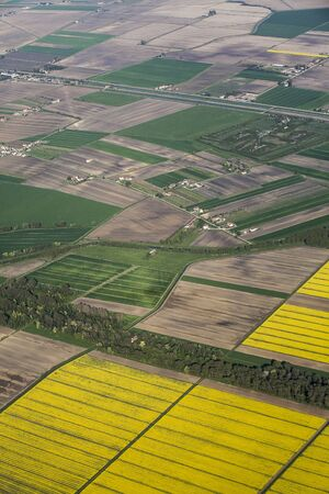 plassen: Aerial view of green and yellow colza fields with some farm houses, canals and roads in The Netherlands.