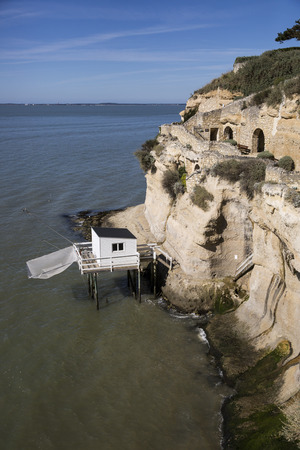 traditional fishermans wooden hut at the bottom of the limestone cliff in the estuary of Gironde, Meschers-sur-Gironde