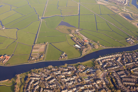 plassen: Aerial view of a village separated from green fields by a canal, The Netherlands