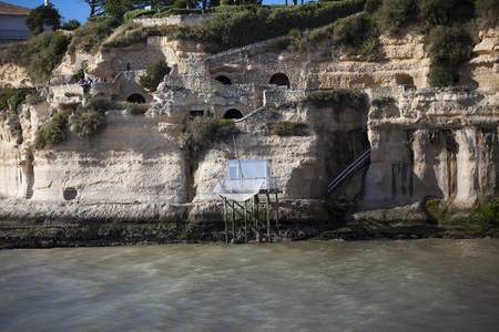 traditional french fishermans wooden hut at the bottom of the limestone cliff in the estuary of Gironde, Meschers-sur-Gironde