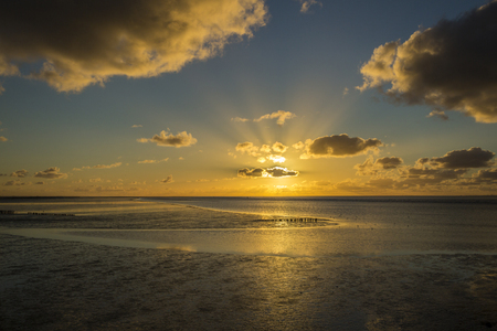 Maritime landscape at sunset with reflection of clouds in low tide water, Waddenzee, Friesland, The Netherlands