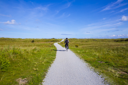 People cycling on a bike path through the dune landscape of Frisian Island Amsland, the Netherlands Stock Photo