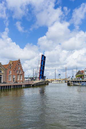 Noorderhaven canal with boats, open bridge and houses in historic old town of Harlingen, Friesland, Netherlands