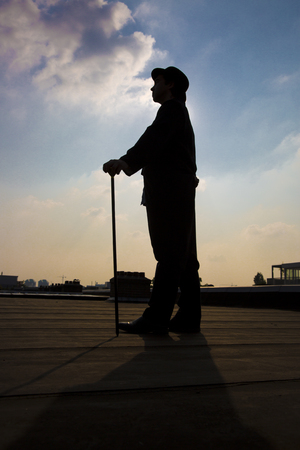 metaphoric: silhouette of a an elegant gentleman wearing a long a coattail with a cane and a  bowler hat