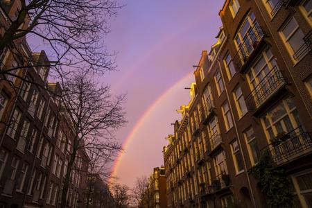 enchanting: Rainbow on a purple sky over street buildings in Amsterdam