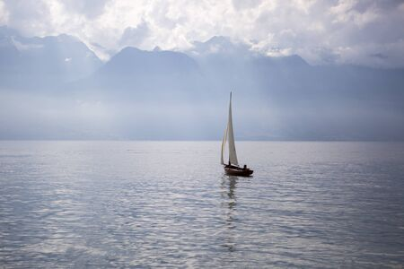 landscape of the Geneva lake  with a boat sailing and the Alps mountains in the background - Vevey, Switzerland Stock Photo