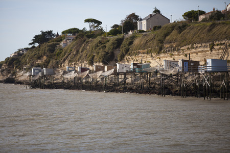 maritimes: traditional french fishermans wooden hut at the bottom of the limestone cliff in the estuary of Gironde, Meschers-sur-Gironde