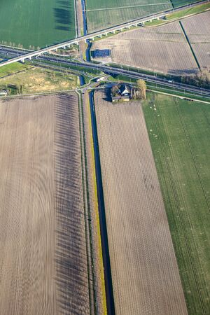 plassen: Aerial view of green fields with a farm house, a canal and motorway road in The Netherlands.