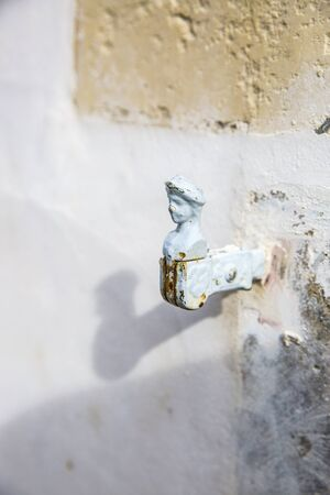 tourniquet: white wall with vintage shutter swing fastener in shape of a man Stock Photo