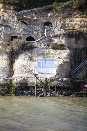 chinese fishing nets: traditional french fishermans wooden hut at the bottom of the limestone cliff in the estuary of Gironde, Meschers-sur-Gironde