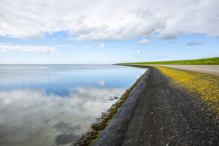 shoreline of Ameland Island, with view over the wadden sea, with clouds reflecting in water at dawn and a bike lane over a dike