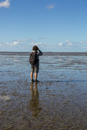 Maritime landscape at low tide water with a man mud walking and looking at the vieuw, Waddenzee, Friesland, The Netherlands Stock Photo