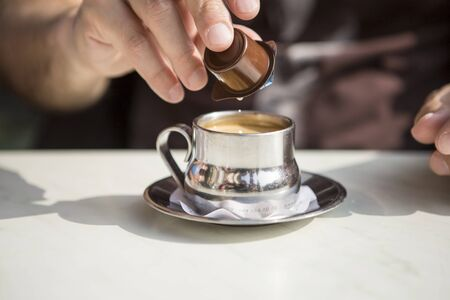 man's: silver cup of coffee with a mans hand pouring cream milk