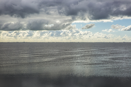 wadden: shoreline of Ameland Island, with view over the wadden sea, with clouds and tourmented sky reflecting in water at dawn