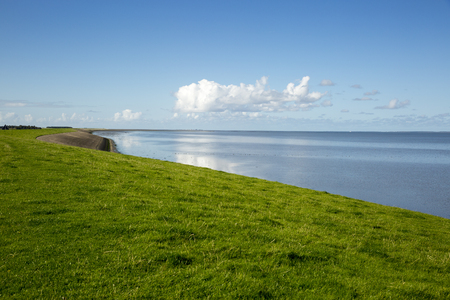Dutch landscape with view on and the wadden sea and a dam with green grass, Wierum, Friesland, The Netherlands Stock Photo