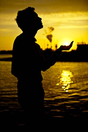 Shadow of a young man holding the sun