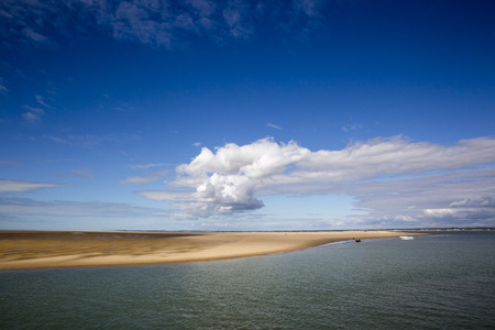 maritime seaside landscape with water, sand bank and white cloud, garonne estuary near Royan, France Stock Photo