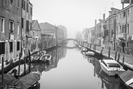 VENICE, ITALY – December 25, 2015: black and white typical romantic canal and street scene, with locals and tourists, in the winter mist in Cannaregio, Venice, Editorial