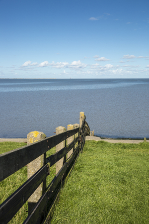 Dutch maritime landscape with wooden fence on a dyke with wadden sea in the background Stock Photo