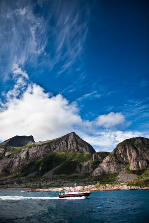 musique: Landscape of a Fjord Norway from the sea with a boat, mountain, blue sky with white clouds Stock Photo