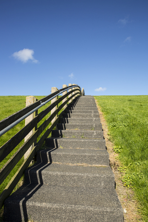 A concrete staircase with wood banister between the green grass of a dike on a sunny day Stock Photo