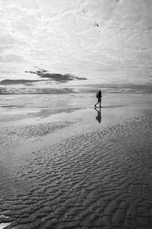 Black and white maritime seaside landscape with man walking on the sand, garonne estuary near Royan, France
