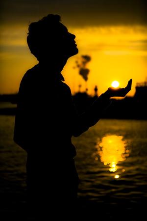 Schaduw van een jonge man die de zon houdt Stockfoto