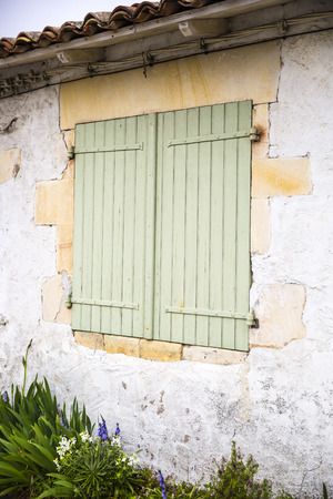security shutters: Closed pale green wooden window shutters. Stock Photo