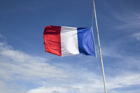 fraternidad: Flag of France floating  in the wind in front of a blue sky background