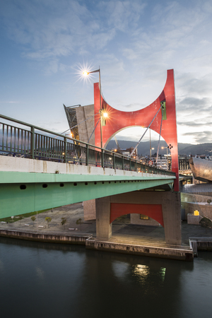 Bilbao, Spain - January 29, 2016: evening view of La Salve Bridge with its Arcos Rojos or Red arches, sculpture design by French Artist Daniel Buren and inaugurated in 1997, Bilbao, Biscay, Basque Country, Spain