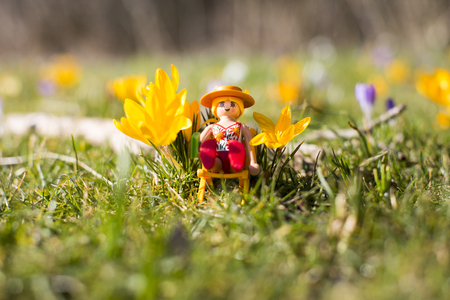 Amsterdam, the Nertherlands. April 12, 2015. Woman sunbathing on a long chair on the grass. Playmobil toy line exist since 1975 and is produced by the German company Brandtaetter.