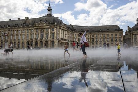 BORDEAUX, FRANCE - April 25, 2015: le Miroir dEau, water mirror near Place de la Bourse designed by landscape artist Michel Corajoud, full of people having fun one of 1st warm spring day of the year