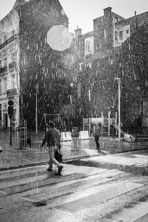 Brussels, Belgium - April 17, 2016: people calmly walking under summer stormy heavy rain in the city center of Brussels
