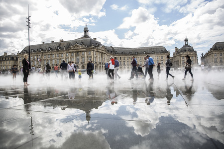 BORDEAUX, FRANCE - April 25, 2015: le Miroir dEau, water mirror near Place de la Bourse designed by landscape artist Michel Corajoud, full of people having fun one of 1st warm spring day of the year