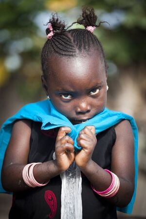 SENEGAL - November 5, 2013: Little shy Senegalese girl living on the island of Sipo in the Sine-Saloum Delta, near Toubacouta