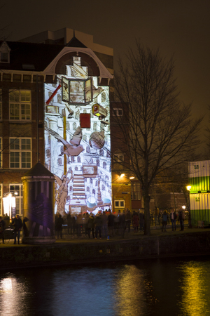 Amsterdam, the Netherlands December 20, 2015: animated video mapping artwork called Canal House from Irma de Vries exhibited at Amsterdam Light Festival 2015 which is dedicated to theme Friendship
