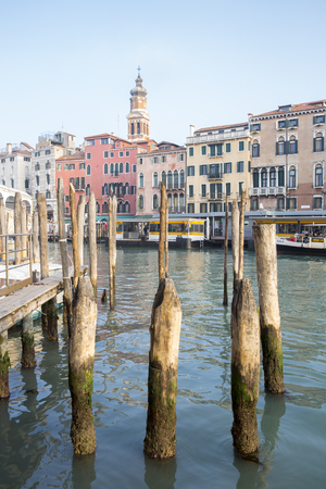 waterbus: VENICE, ITALY - December 25, 2015: View on the Grand Canal with its mooring poles and in the background the waterbus or vaporetto stop