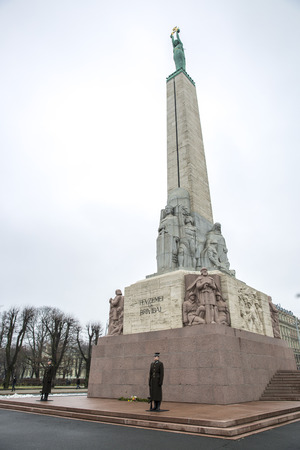 Riga, Latvia - February, 13 2016: Freedom Monument at daytime. The statue represents a woman holding three gold stars which symbolise three regions of Latvia. Redakční