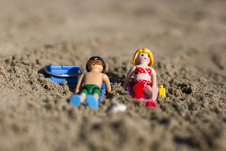 Amsterdam, the Nertherlands. April 12 3, 2015. A man and a woman sun tanning on the sand. Playmobil toy line exist since 1975 and is produced by the German company Brandtaetter. Editorial