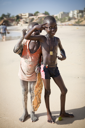 SENEGAL, Ndayane - November 9, 2013: Unidentified Senegalese children on the beach of Ndayane, playing and waiting for their father to come back from fishing . Despite poverty, Senegal kids stay smiling. Editorial