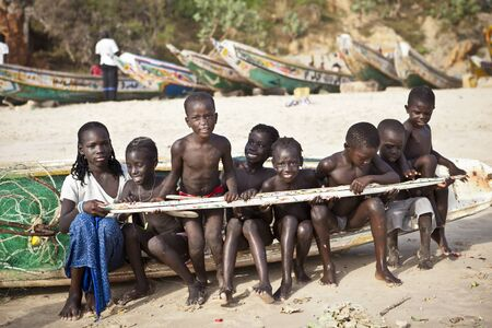 senegalese: SENEGAL, Ndayane – November 9, 2013: Unidentified Senegalese children on the beach of Ndayane, playing and waiting for their father to come back from fishing . Despite poverty, Senegal kids stay smiling. Editorial