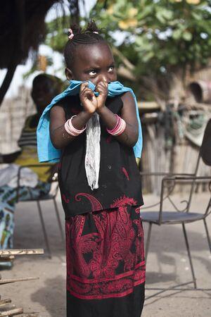 senegalese: SENEGAL - November 5, 2013: Little shy Senegalese girl living on the island of Sipo in the Sine-Saloum Delta, near Toubacouta