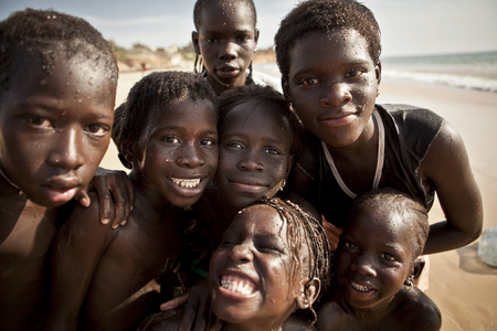 senegalese: SENEGAL, Ndayane - November 9, 2013: Unidentified Senegalese children on the beach of Ndayane, playing and waiting for their father to come back from fishing . Despite poverty, Senegal kids stay smiling. Editorial