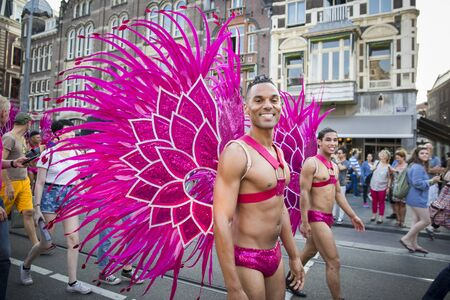 Amsterdam, the Netherlands - July 23, 2016: handsome young men dressed as pink butterflies at Pride Walk, demonstration parade from Vondelpark to Dam Square, Pink Saturday Gay Euro Pride celebrations