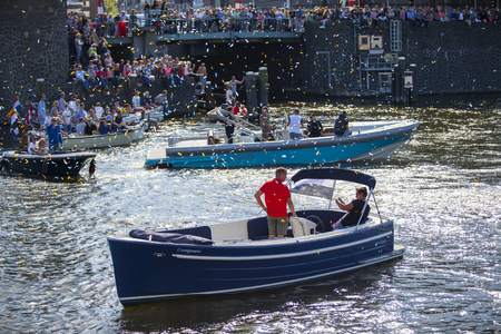 Amsterdam, the Netherlands - August 06, 2016: people watching the Euro Pride 2016 Gay Pride Parade from their boat. Gay Pride is an annual event for the protection of human rights and civil equality
