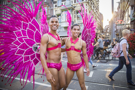 identidad cultural: Amsterdam, the Netherlands - July 23, 2016: handsome young men dressed as pink butterflies at Pride Walk, demonstration parade from Vondelpark to Dam Square, Pink Saturday Gay Euro Pride celebrations