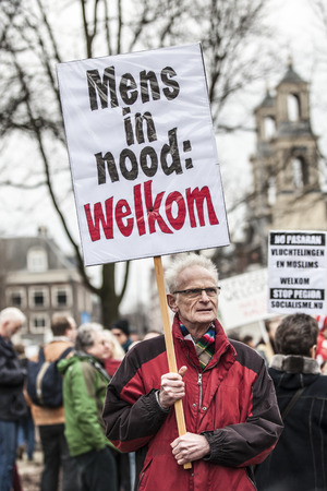 Amsterdam, The Netherlands - February 6,2016: public multi-cultural demonstration organized to protest against racism and islamophobia named Refugees welcome, racism not! a man holds a sign saying People in urgency, welcome