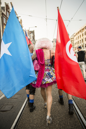 identidad cultural: Amsterdam, the Netherlands - July 23, 2016: drag queen surrounded with 2 men holding somalian and turkish flags at Pride walk, demonstration parade from Vondelpark to Dam Square during Pink Saturday Gay Euro Pride celebrations