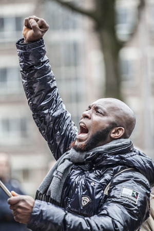 Amsterdam, The Netherlands - February 6,2016: public multi-cultural demonstration organized to protest against racism and islamophobia named Refugees welcome, racism not! A black man is raising his fist Editorial